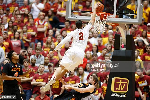 Abdel Nader of the Iowa State Cyclones dunk the ball as Joe Burton and Mitchell Solomon of the Oklahoma State Cowboys defend in the second half of...