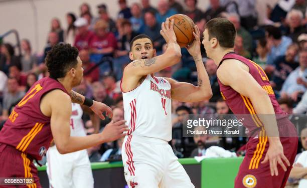 Abdel Nader of the Maine Red Claws looks for an open teammate as Stephan Hicks and Tyler Hansbrough play defense for the Fort Wayne Mad Ants Monday...