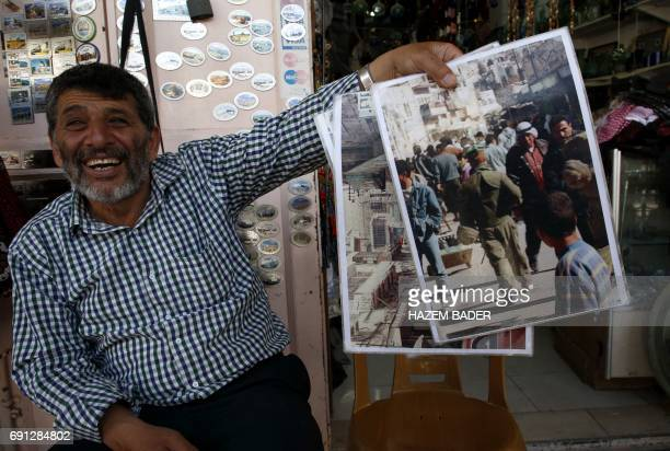 Abdel Raouf alMohtasseb a 59yearold Palestinian man who runs a stall in the old town of Hebron holds a photo on May 8 2017 showing the market full of...