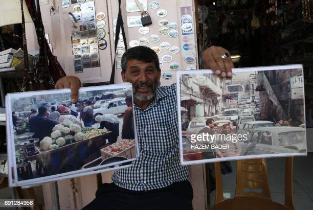 Abdel Raouf alMohtasseb a 59yearold Palestinian man who runs a stall in the old town of Hebron hold photos on May 8 2017 showing the market full of...