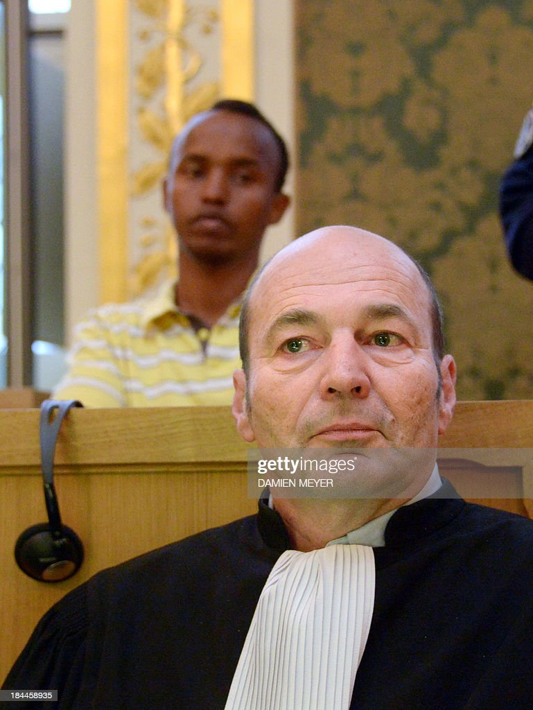 Abdelkader Osmane Ali (background), one of the three Somali pirates arrested by French soldiers in 2009 Mahmoud Abdi Mohammed waits in the accused box, behind his lawyer Ronan Appere, on October 14, 2013 at Rennes' courthouse, prior to the opening hearing of their trial for hijacking a yacht in 2009. French troops stormed the Tanit sailboat on April 10, 2009 and captured the trio in a bid to free Florent Lemacon, his wife, their three-year-old son and two others.