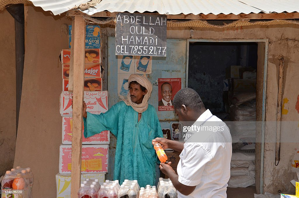 Abdellah Ould Hamaid, a Tuareg, who returned to Gao two months ago after fleeing the city fearing reprisals from the population, sells sodas in Gao on July 26, 2013. An ancient capital of West Africa's Songhai empire, the Malian city of Gao was for centuries a bustling trade centre for Tuareg nomads taking lucrative camel caravans of gold, salt and dates across the Sahara desert. These days, visitors are unlikely to find much business being done, the dusty tree-lined avenues emptied of many of the mud-brick shops which thrived before Islamist invaders occupied the city last year.