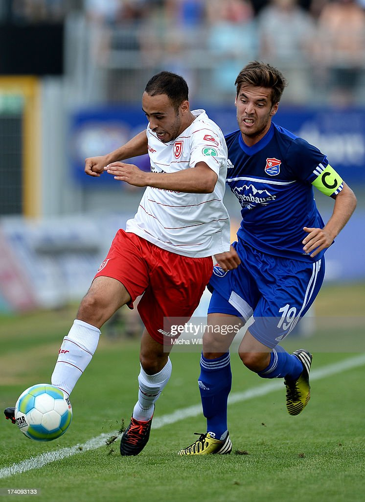Abdenour Amachaibou (L) of Regensburg is challenged by Maximilian Welzmueller of Unterhaching during the Third League match between Jahn Regensburg and SpVgg Unterhaching at Jahnstadion on July 20, 2013 in Regensburg, Germany.