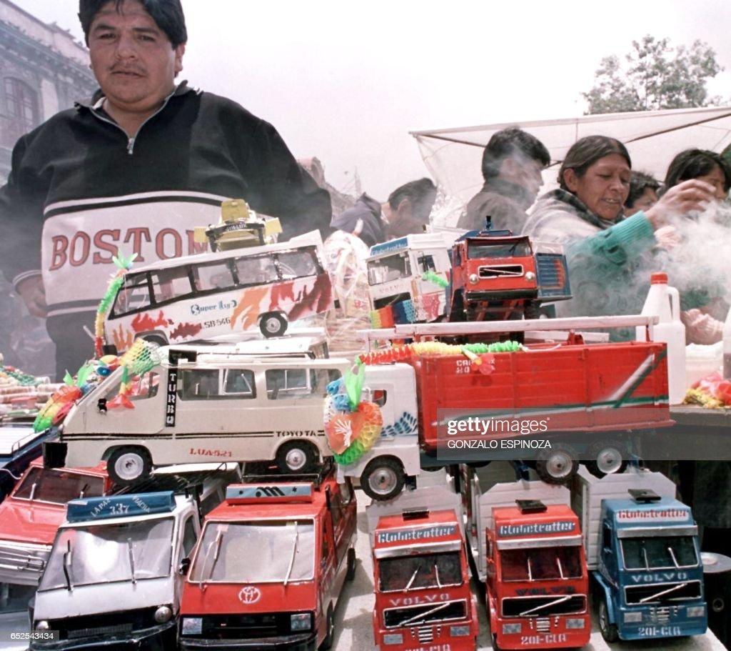 Abdon Rojas sells miniature cars and trucks for the Festival of Alasitas. Abdon Rojas exhibe sus camiones y buses en miniatura, el 24 de enero del 2000 en La Paz, durante, la inauguracion de la fiesta de 'Alasitas', en la cual miles de creyentes compran bienes materiales miniaturizados, en la creencia de que el Dios de esta tradicion, el 'Ekeko' o Dios de la abundancia segun creencias de la cultura aymara, los convertira en realidad en un futuro proximo. AFP PHOTO / Gonzalo ESPINOZA /