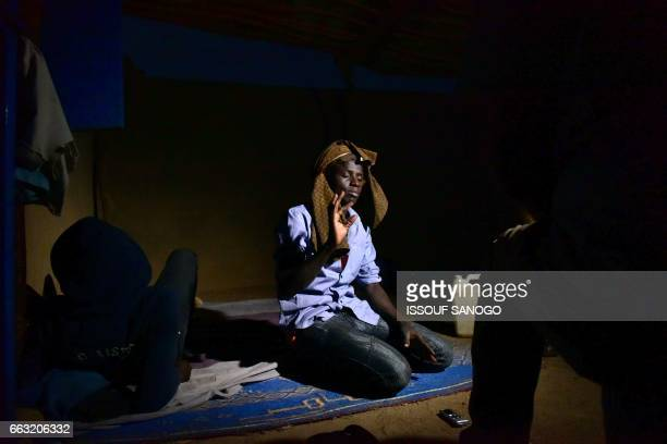 Abdoulaye a young senegalese man gestures as he speaks while waiting in a 'ghetto' of the city of Agadez northern Niger on March 31 in order to reach...
