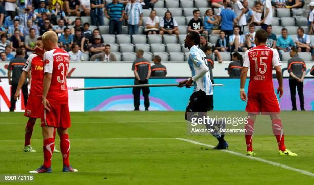 Abdoulaye Ba carries a flagpole off the pitch of 1860 Muenchen during the Second Bundesliga Playoff second leg match betweenTSV 1860 Muenchen and...