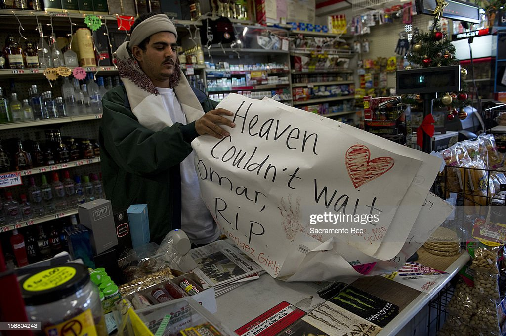 Abdul Awnallah holds a sign on December 11, 2012, that was posted at the Paisano Market in south Stockton, California, where his cousin, Majad 'Omar' Awnallah, was killed in November, after a man entered the store and shot him.