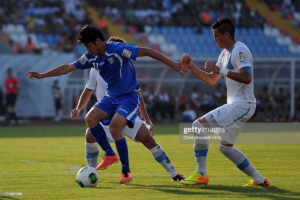 Abdul Aziz Yusupov (L) of Uzbekistan is challenged by Jose Gimenez of Uruguay during the FIFA U20 World Cup Group F match between Ukbekistan and Uruguay at Akdeniz University Stadium on June 29, 2013 in Antalya, Turkey.