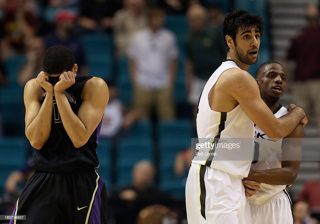 Abdul Gaddy (L) #0 of the Washington Huskies is dejected, as Arsalan Kazemi #14 and Johnathan Loyd #10 of the Oregon Ducks embrace in the closing seconds of overtime during the quarterfinals of the Pac 12 Basketball Tournament at the MGM Grand Garden Arena on March 14, 2013 in Las Vegas, Nevada. Oregon defeated Washington 80-77 in overtime.