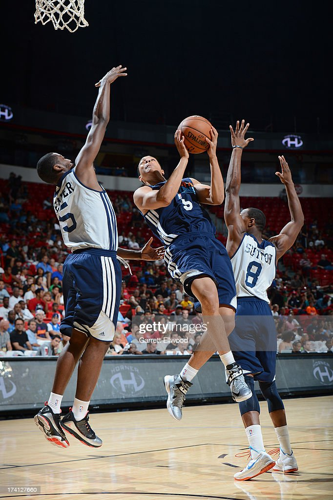 Abdul Gaddy #5 of the Charlotte Bobcats goes to the basket against KyleWeaver #5 and Dominique Sutton #8 of the D-League Select Team during the NBA Summer League game between the Charlotte Bobcats and the D-League Select Team on July 20, 2013 at the Cox Pavilion in Las Vegas, Nevada.