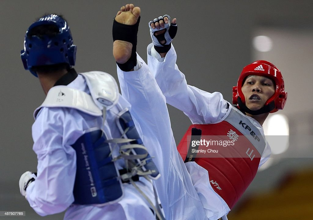 Abdul Hemi Mohd (R) of Malaysia tries to kick Samuel Thomas Harper Morrison of the Philippines during the Quarter Finals of the Men's 68-74 kg TaeKwondo Competition during the 2013 SEA Games at the Wunna Theikdi Indoor Stadium on December 18, 2013 in Nay Pyi Taw, Burma.