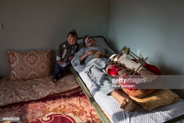 Abdul Hussain Ayoobi is seen at home with his son Ali Akbar who is trying to understand why his father hurts so much all the time Abdul a carpenter...