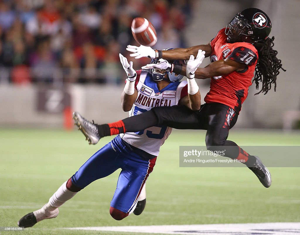 Abdul Kanneh #14 of the Ottawa Redblacks deflects an intended pass to Duron Carter #89 of the Montreal Alouettes during a CFL game at TD Place Stadium on September 26, 2014 in Ottawa, Ontario, Canada.