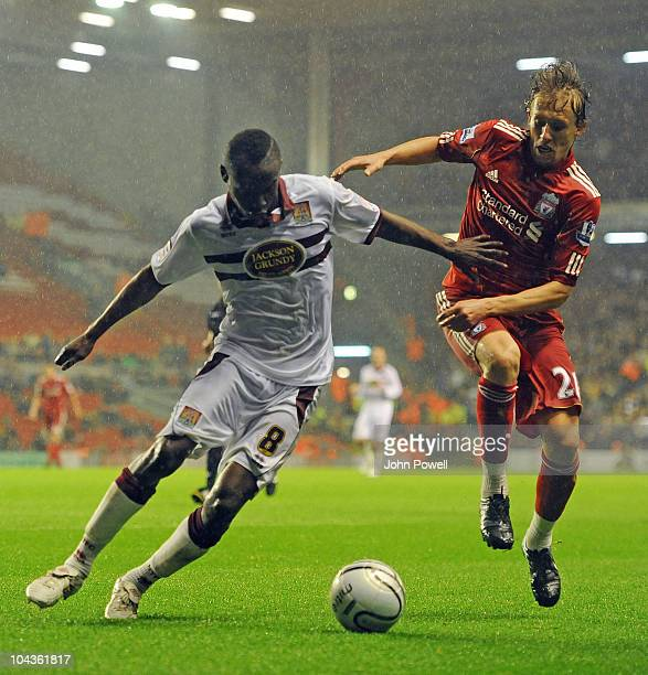 Abdul Osman of Northampton Town tussles with Lucas of Liverpool during the Carling Cup 3rd round game between Liverpool and Northampton Town at...