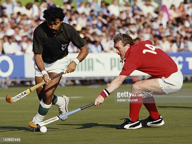 Abdul Rashid of Pakistan is tackled by Norman Hughes of England during their Pool A match at the 6th FIH Men's Field Hockey World Cup on 11th October...