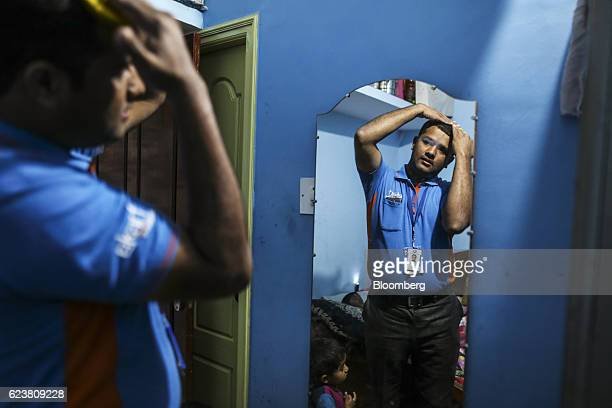 Abdul Saleem a deliveryman known as a Wishmaster for Flipkart Online Services Pvt's Ekart Logistics service adjusts his hair while preparing for work...