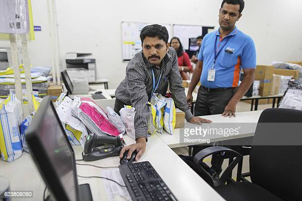 Abdul Saleem a deliveryman known as a Wishmaster for Flipkart Online Services Pvt's Ekart Logistics service right watches a colleague use a computer...