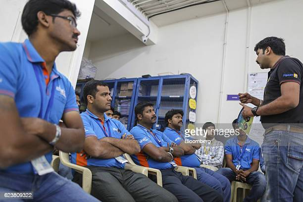 Abdul Saleem a deliveryman known as a Wishmaster for Flipkart Online Services Pvt's Ekart Logistics service second left listens to a briefing at the...