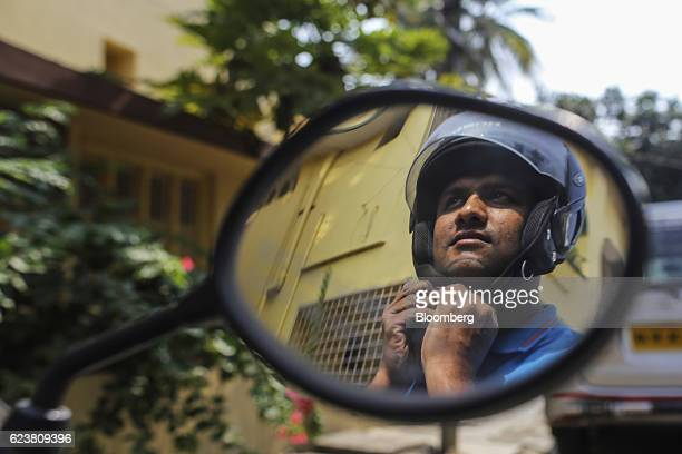 Abdul Saleem a deliveryman known as a Wishmaster for Flipkart Online Services Pvt's Ekart Logistics service putting on his helmet is reflected in the...