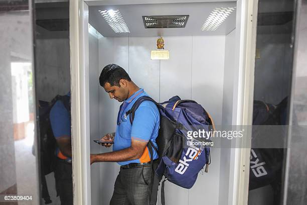 Abdul Saleem a deliveryman known as a Wishmaster for Flipkart Online Services Pvt's Ekart Logistics service uses a smartphone as he rides an elevator...