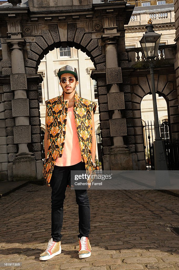 Abdulla Al-Abdulla of Qatar wears Opening Ceremony jacket by Kenzo, salmon coloured top by Urban Outfitters, 7 for All Mankind jeans, accessorised with Karl-Alley cap, Urban Outfitter sunglasses, bracelets by Links of London, Tateossian, Vottega Venetta skulls bracelet from Madison Ave, Kossak inspired Bulgari ring worn as a pendant, customised hi-top sneakers designed by Abdulla Al-Abdulla at London Fashion Week Fall/Winter 2013/14 on February 17, 2013 in London, England.