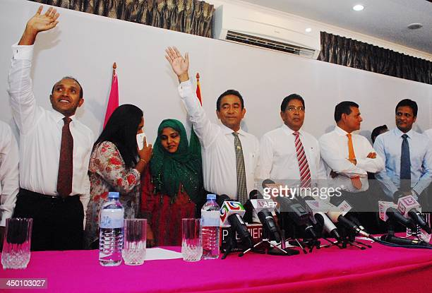 Abdulla Yameen waves as he stands with other party offcials during a press conference at a local hotel in Male early on November 17 2013 after...