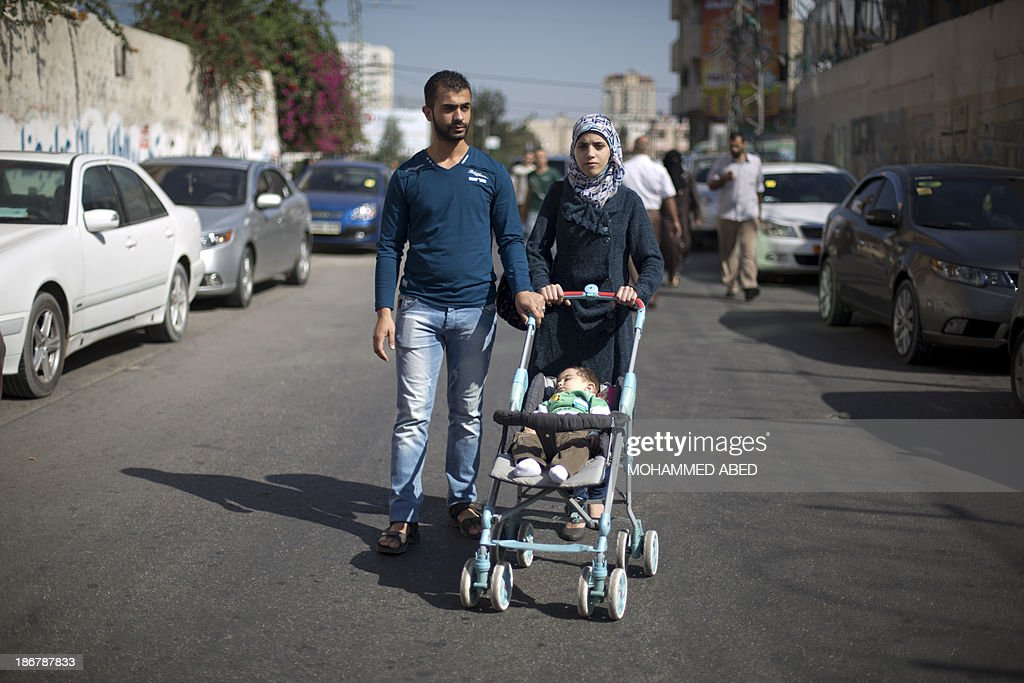 Abdullah Elian, 26, his wife Walla Abbud, 19, and their two-month-old son Mohammed walk in Gaza City, on October 28, 2013. They have fled their native Syria in April 2013. They left Damascus by plane to Cairo then crossed into the Gaza Strip through the Rafah crossing terminal. They live in a rented flat in the Gaza Strip southwestern town of Zahra.
