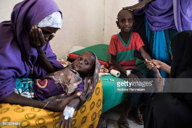 Abdullahi Mohamud cries next to his mother Sahro Mohamed Mumin and brother Abdulrahman Mahamud as a nurse struggles to find a vein for an injection...