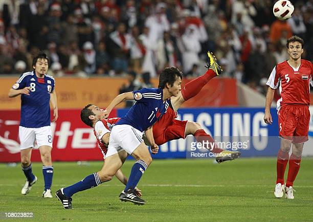 Abdulrazak Al Husein clears the ball away from Ryoichi Maeda of Japan during the AFC Asian Cup Group B match between Syria and Japan at Qatar Sports...