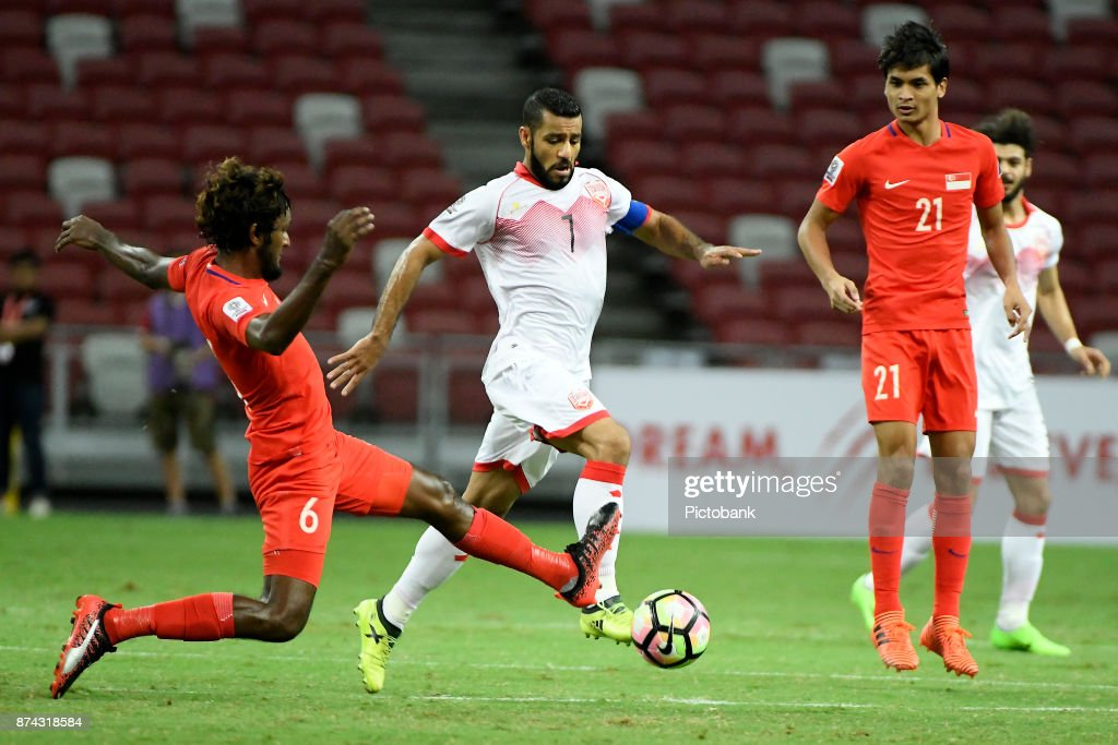 Abdulwahab Ali Alsafi of Bahrain runs with the ball while Madhu Mohana of Singapore (L) tries to stop him during the Asian Cup Qualifier match between Singapore and Bahrain at the Singapore Sports Hub on November 14, 2017, in Singapore, Singapore.