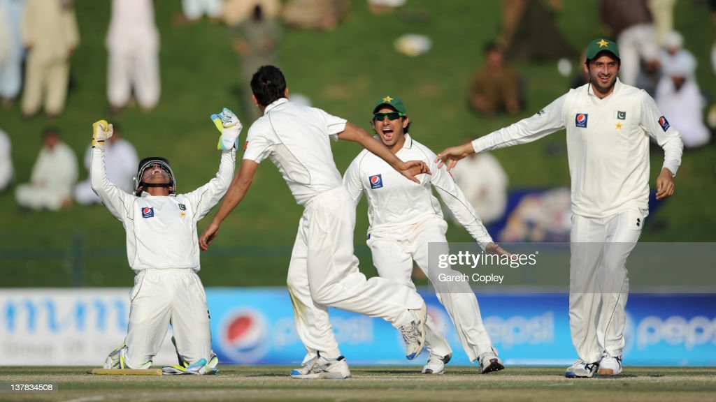 Abdur Rehman of Pakistan celebrates with Adnan Akmal, Saeed Ajmal and Junaid Khan after dismissing James Anderson of England at Sheikh Zayed Stadium on January 28, 2012 in Abu Dhabi, United Arab Emirates.