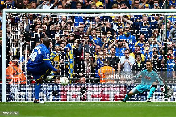 Abebayo Akinfenwa of Wimbledon scores his sides second goal from a penalty during the Sky Bet League Two Play Off Final match between Plymouth Argyle...