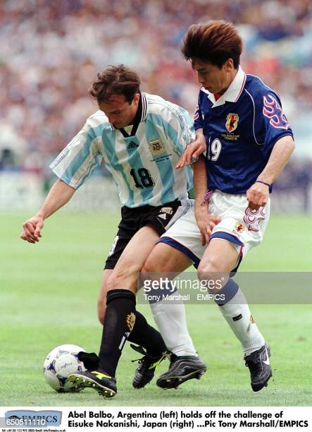 Abel Balbo of Argentina holds off the challenge of Eisuke Nakanishi of Japan