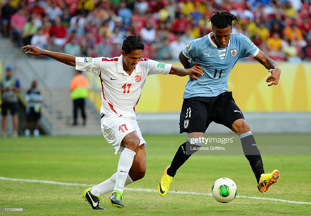 Abel Hernandez of Uruguay battles for the ball with Jonathan Tehau of Tahiti during the FIFA Confederations Cup Brazil 2013 Group B match between Uruguay and Tahiti at Arena Pernambuco on June 22, 2013 in Recife, Brazil.