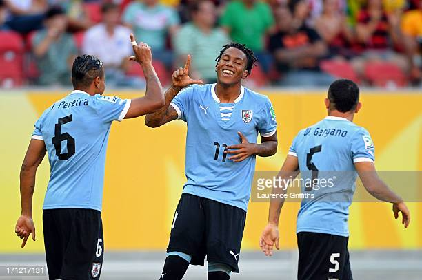 Abel Hernandez of Uruguay celebrates with teammates Alvaro Pereira and Walter Gargano after scoring in the 2nd minute against Tahiti during the FIFA...