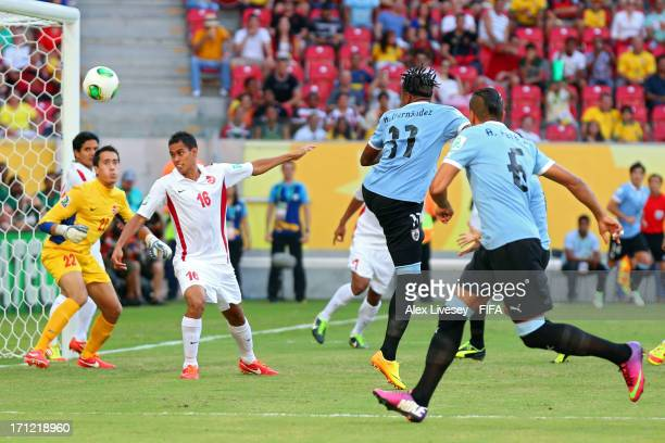 Abel Hernandez of Uruguay hits a header to score a goal in the 2nd minute against Ricky Aitamai and Gilbert Meriel of Tahiti during the FIFA...