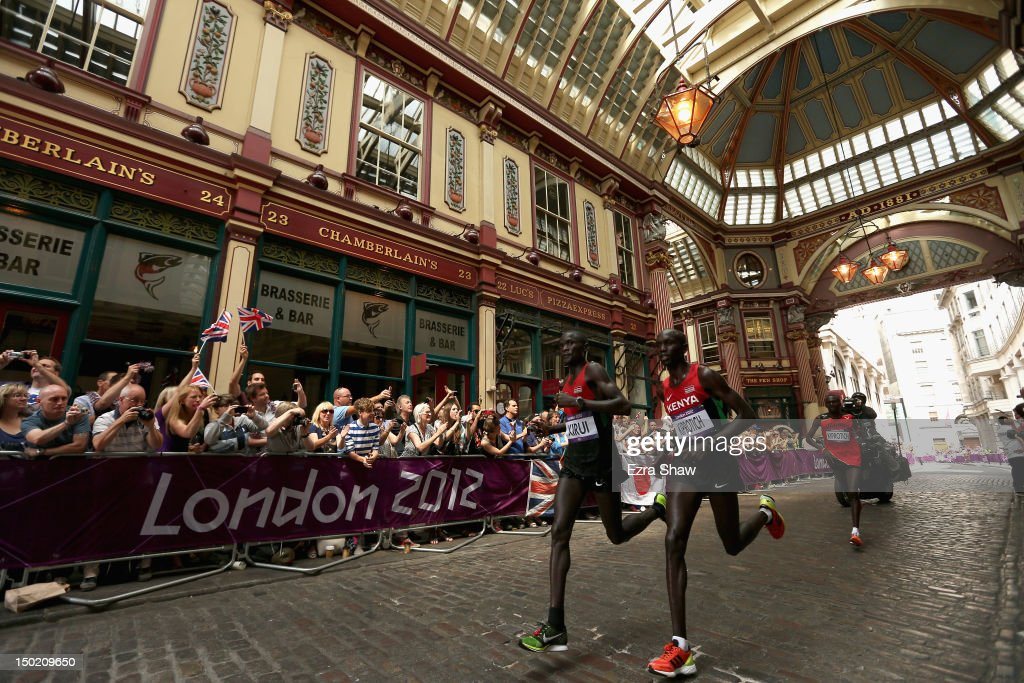 Abel Kirui of Kenya, Wilson Kipsang Kiprotich of Kenya and Stephen Kiprotich of Uganda run through Leadenhall Market as they compete in the Men's Marathon on Day 16 of the London 2012 Olympic Games on the streets of London on August 12, 2012 in London, England.