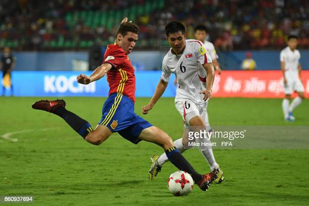 Abel Ruiz of Spain shoots as Han Kyong Hun of Korea DPR challenges during the FIFA U17 World Cup India 2017 group D match between Spain and Korea DPR...