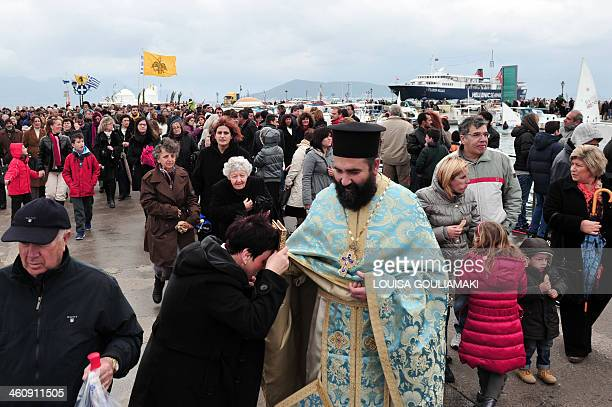 Abeliever kisses a holy icon during the ceremony of the blessing of the waters marking orthodox Epiphany Day at the port of Aegina island near Athens...