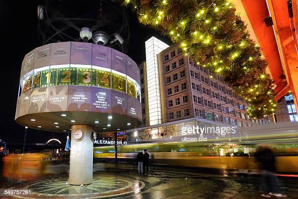 Abendszene auf dem Alexanderplatz in Berlin Beim Weihnachtsmarkt stehen geschmückte Buden neben der Weltzeituhr