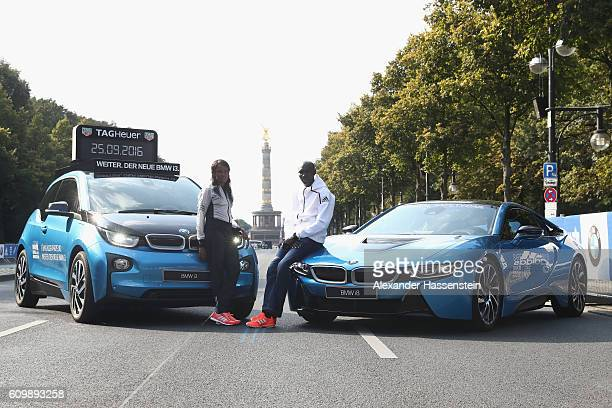 Aberu Kebede of Ethiopia and former world record holder Wilson Kipsang of Kenya poses in front of the BMW i3 and BMW i8 at the Siegessaeule on...