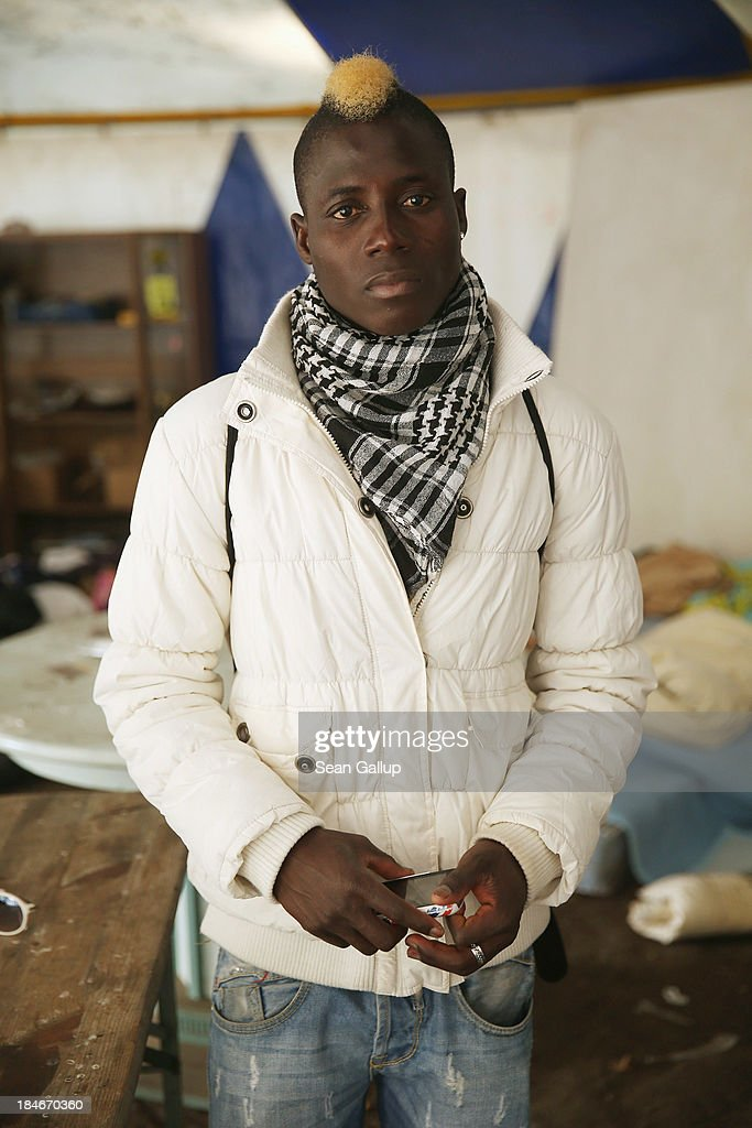 Abidal, 24, who is a refugee from Burkina Faso, poses for a photograph in a tent at the makeshift camp where he and approximately 100 other refugees are living at Oranienplatz in Kreuzberg district on October 14, 2013 in Berlin, Germany. Abidal came to Europe in 2011 after a two-day journey on a rickety boat with approximately 360 other refugees from Libya to Lampedusa, during which he says about 15 passengers drowned. After receiving help and documentation from the Red Cross he spent time in Italy, and later made his way to Germany, where he has been nine months and where he hopes to one day receive residence status and a job. Berlin authorities have tolerated the camp at Oranienplatz and have promised to move the refugees to proper housing ahead of the coming winter.