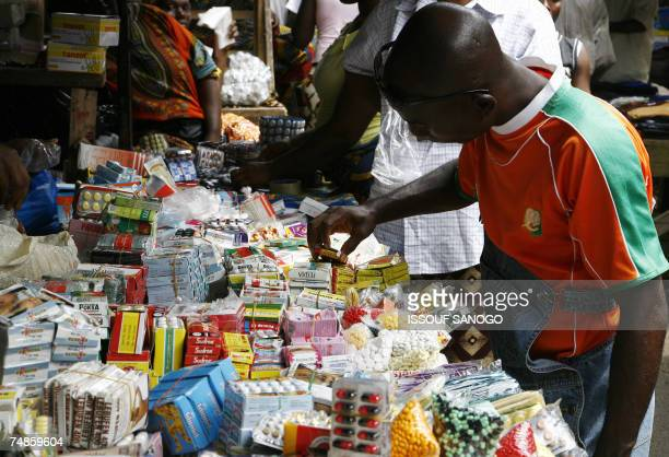 A man buys smuggled and/or counterfeit medicine 14 June 2007 on the Adjame market in Abidjan Ivorian pharmacists are worried about the multiplication...