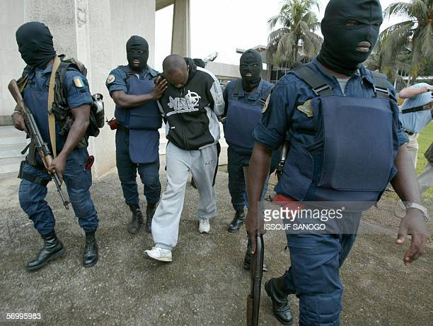 Clad in grey tracksuit French alleged gang leader Youssouf Fofana is escorted by hooded Ivory Coast's Gendarme officers on his way to board a...