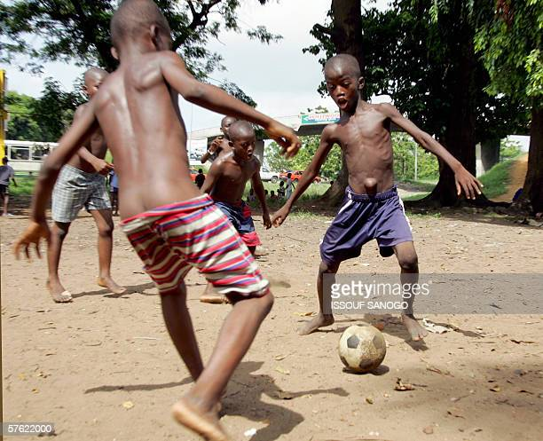 Ivorian boys play street soccer 16 May 2006 in a poor neighbourhood of Abidjan Thousands of young football players are conned each year by...