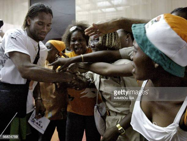Ivory star striker and Chelsea player Didier Drogba shakes hands with Ivory Coast's fans 11 February 2006 at the Felix Houphouet Boigny airport in...