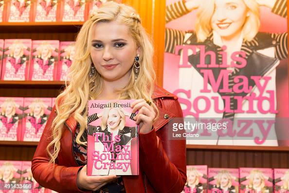 Abigail Breslin shows a copy of her new book 'This May Sound Crazy' during a book signing on October 4 2015 in Metairie Louisiana