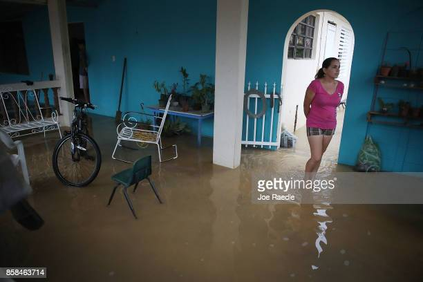 Abigail Maldonado stands in her home inundated with water after a heavy rain passed through following Hurricane Maria on October 6 2017 in Utuado...