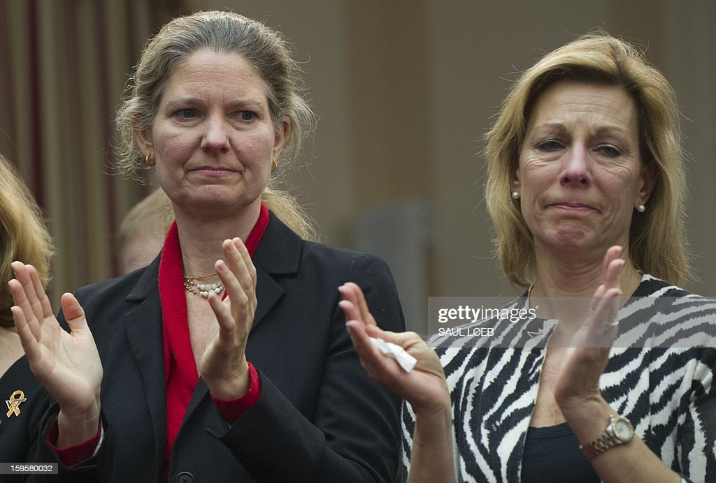 Abigail Spangler (L), Founder of Protest Easy Guns, and Martina Leinz, President of the Million Mom March, applaud during a meeting of the House Democratic Steering and Policy Committee about gun safety on Capitol Hill in Washington, DC, on January 16, 2013. AFP PHOTO / Saul LOEB