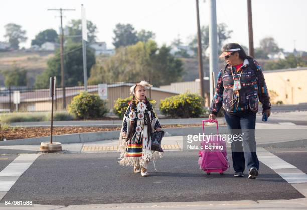 Abigayle Kordatzky walks with her grandma on their way to participate in a tribal ceremonial dancing competition at the Pendleton RoundUp on...